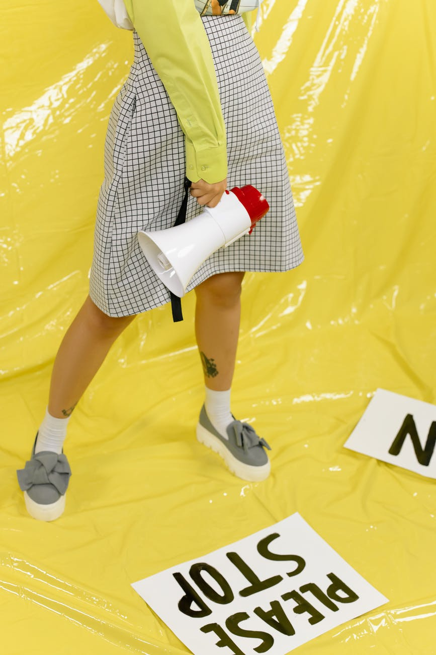 A woman standing against a yellow background holding a megaphone.