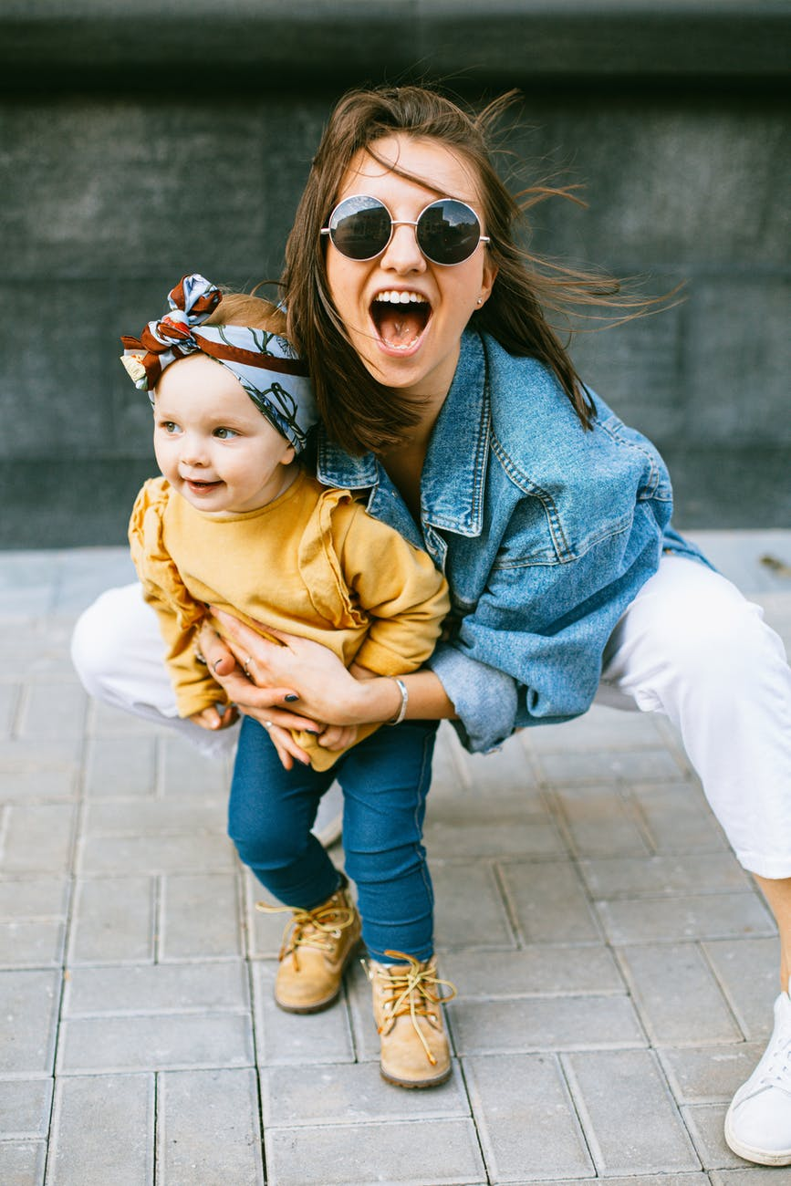 White woman with dark hair, sunglasses and a denim jacket is making a silly face at the camera while snuggling a toddler girl with a yellow shirt and large head band.