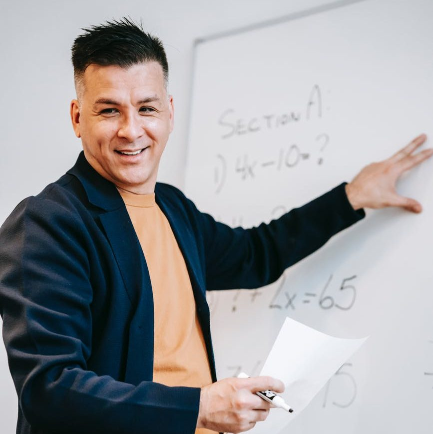 A man in a black blazer explains a concept at the white board in front of a classroom.