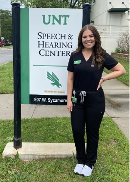 """Image description: Rozanne stands in front of a sign that reads """"UNT Speech & Hearing Center"""" while smiling and wearing black scrubs with her name tag and badge clipped to her."""